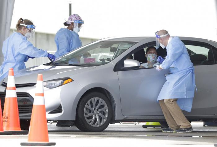 Healthcare workers gather information before conducting an antigen test, Wednesday, Aug. 5, 2020, at a COVID-19 testing site outside Hard Rock Stadium in Miami Gardens, Fla.