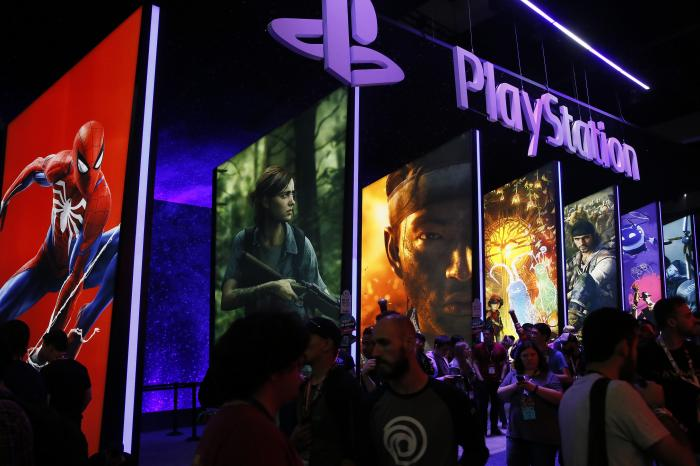 People stand online next to the PlayStation booth at the 24th Electronic Entertainment Expo E3 at the Los Angeles Convention Center.
