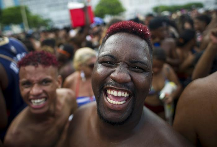"""In this Jan. 12, 2020 file photo, revelers smile as they look on the camera during the """"Bloco da Favorita"""" street party on Copacabana beach, Rio de Janeiro, Brazil."""