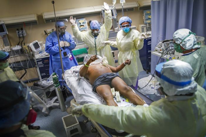 Nurses and doctors clear the area before defibrillating a patient with COVID-19 who went into cardiac arrest at St. Joseph's Hospital in Yonkers, N.Y.