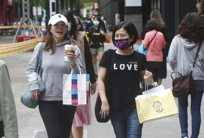 People wear face masks to protect against the spread of the coronavirus as they walk through a shopping district in Taipei, Taiwan.