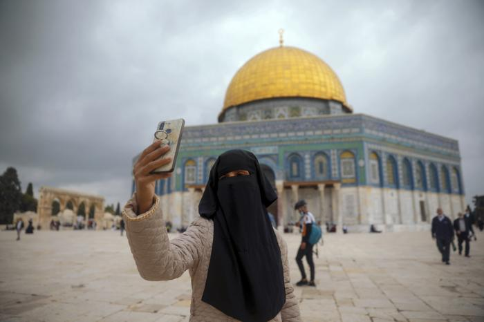 A Muslim woman takes a photo next to the Dome of the Rock Mosque in the Al Aqsa Mosque compound in Jerusalem's old city, Friday, Nov. 6, 2020.
