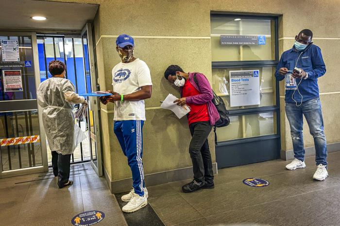 People who were just tested for COVID-19 wait in line to make payment for the test at a private laboratory in Johannesburg, South Africa.