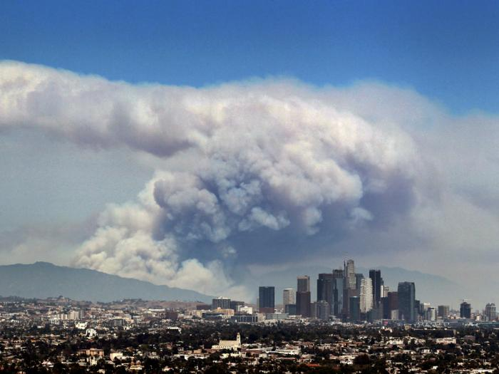 In this Monday, June 20, 2016 file photo, smoke from wildfires burning in Angeles National Forest fills the sky behind the Los Angeles skyline