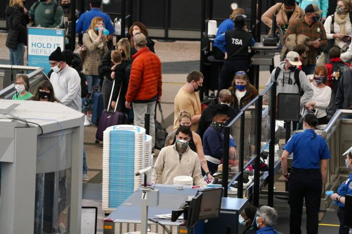 Travelers wear face coverings as they queue up at the north security checkpoint in the main terminal of Denver International Airport, in Denver.