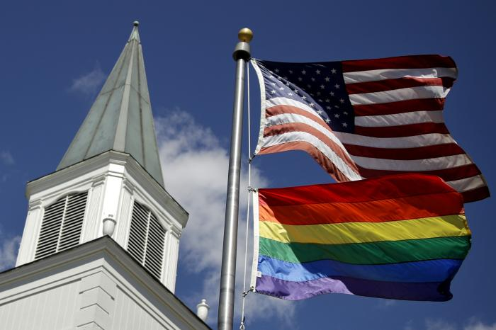 A gay pride rainbow flag flies along with the U.S. flag in front of the Asbury United Methodist Church in Prairie Village, Kan.