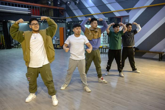 Members of the Chinese music group Produce Pandas, from left, Husky, Otter, Mr. 17, Cass, and DING strike a pose while practicing dance choreography during rehearsals in Beijing.