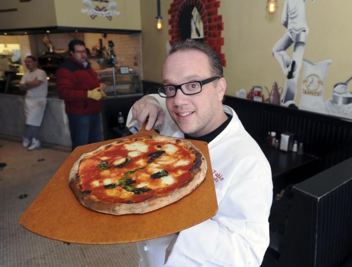 Bruno DiFabio displays a Margherita pizza at ReNapoli Pizzeria & Chicago Italian Beef in Old Greenwich, Conn.